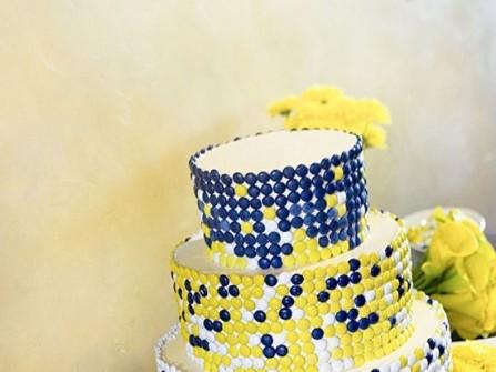 Bánh cưới trang trí kẹo màu vàng và xanh navy