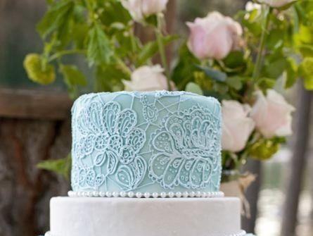 Bánh cưới với thiết kế hoa xanh xung quanh mặt bánh