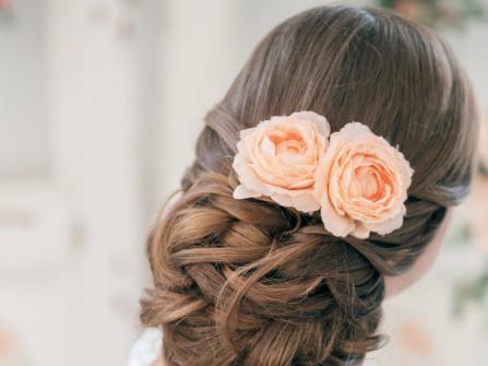 Tóc cô dâu búi thấp cài hoa hồng sang trọng