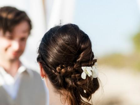 Tóc cô dâu thắt bím búi thấp cài hoa nhỏ