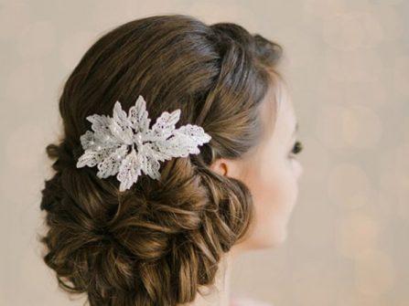 Tóc cô dâu đẹp uốn lọn, búi thấp kết phụ kiện ren